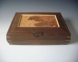 This shows one of my handmade wooden jewelry boxes that is flat and is made of black maple with a burl lid