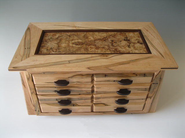Handcrafted wooden jewelry box made of wormy maple with four drawers to hold earrings