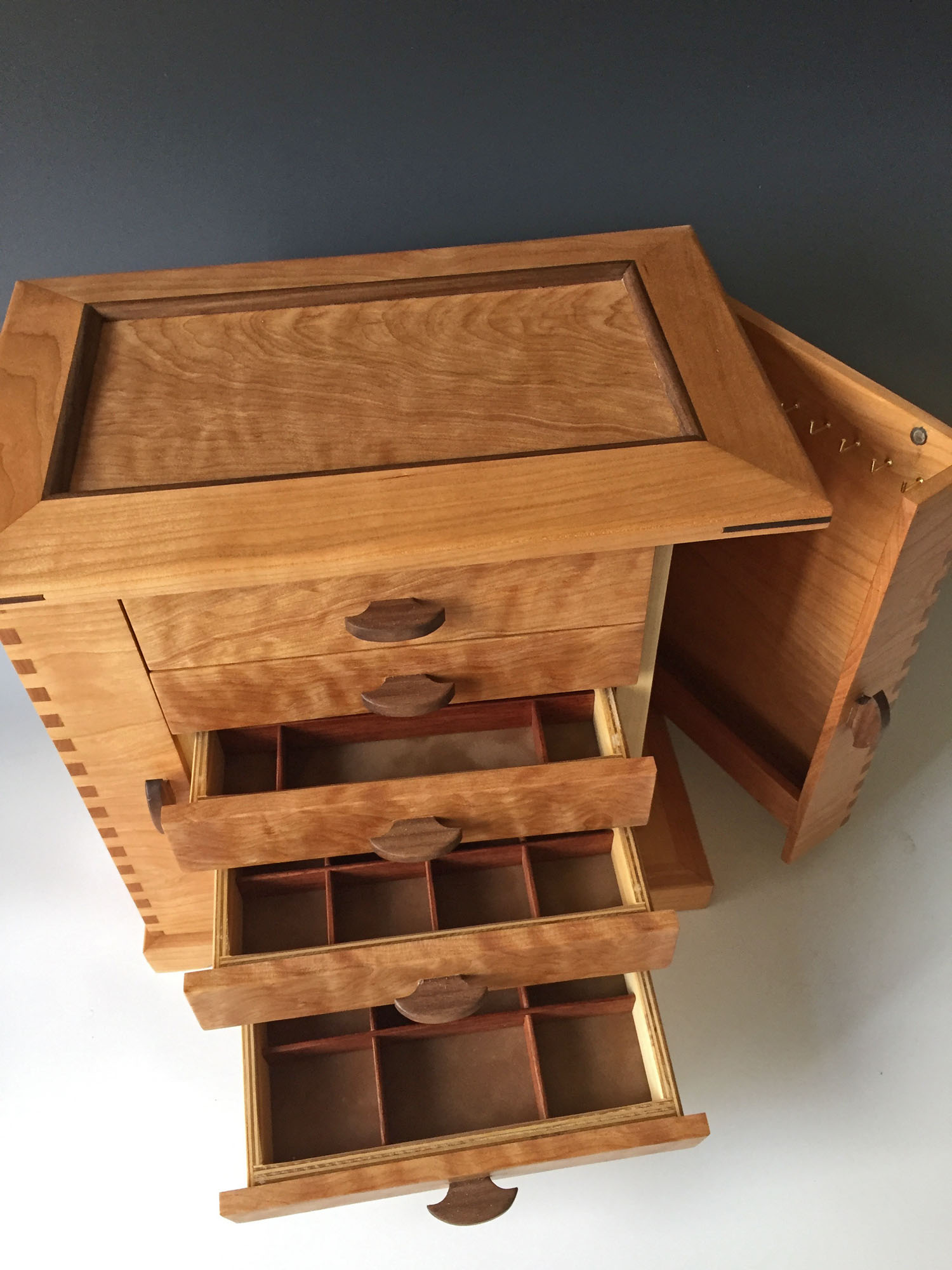 A handmade jewelry box with numerous drawers open to show the extensive storage options, plus a side door to hang necklaces.