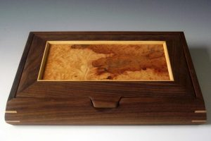 Decorative wooden box made of black walnut with a lid made of burl