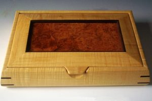 Handcrafted wooden box made of curly maple wood with a lid made of elm burl