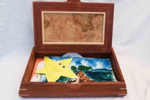 A handmade decorative wooden box is shown open and inside it holds kids art and paintings