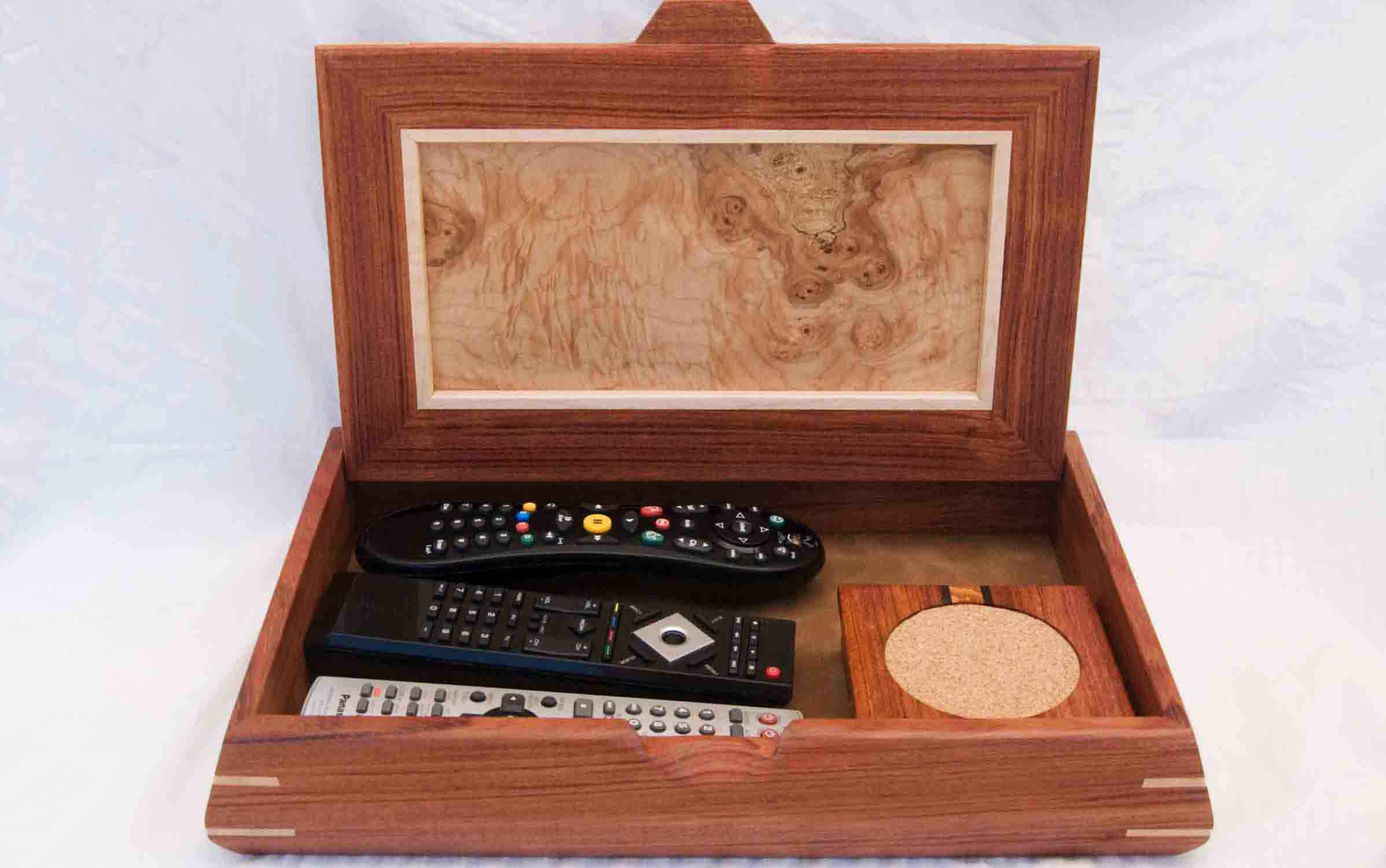A handcrafted wooden decorative box shown holding remote controls and coasters