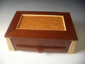 Box-shaped jewelry box with angled legs, a lid that lifts up and a drawer that pulls out