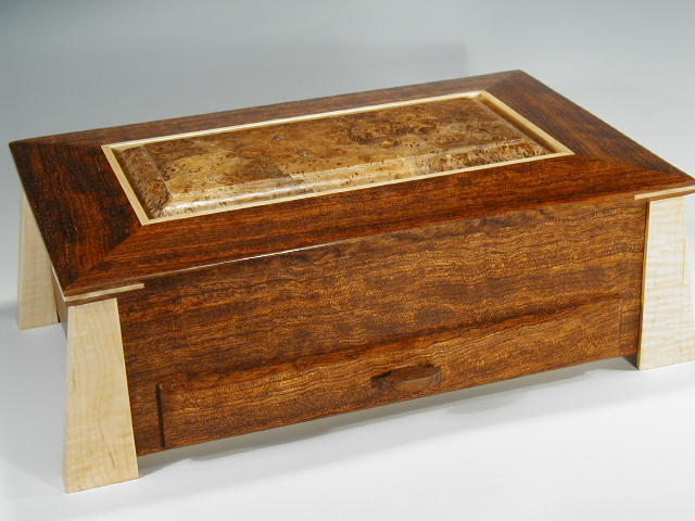 Handmade modern jewelry box made of bubinga and curly maple woods; it is low and wide with angled legs, a drawer, and a lid that lifts open