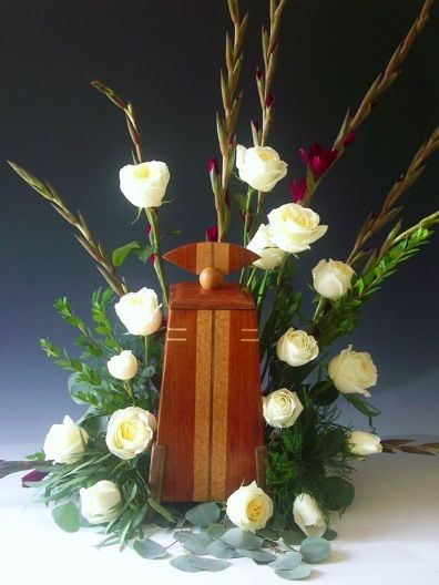 Handmade wooden cremation urn surrounded by white flowers