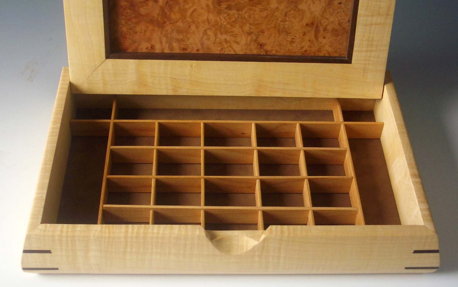 Mens jewelry box made of exotic woods that is shown open to reveal cubed compartments for jewelry
