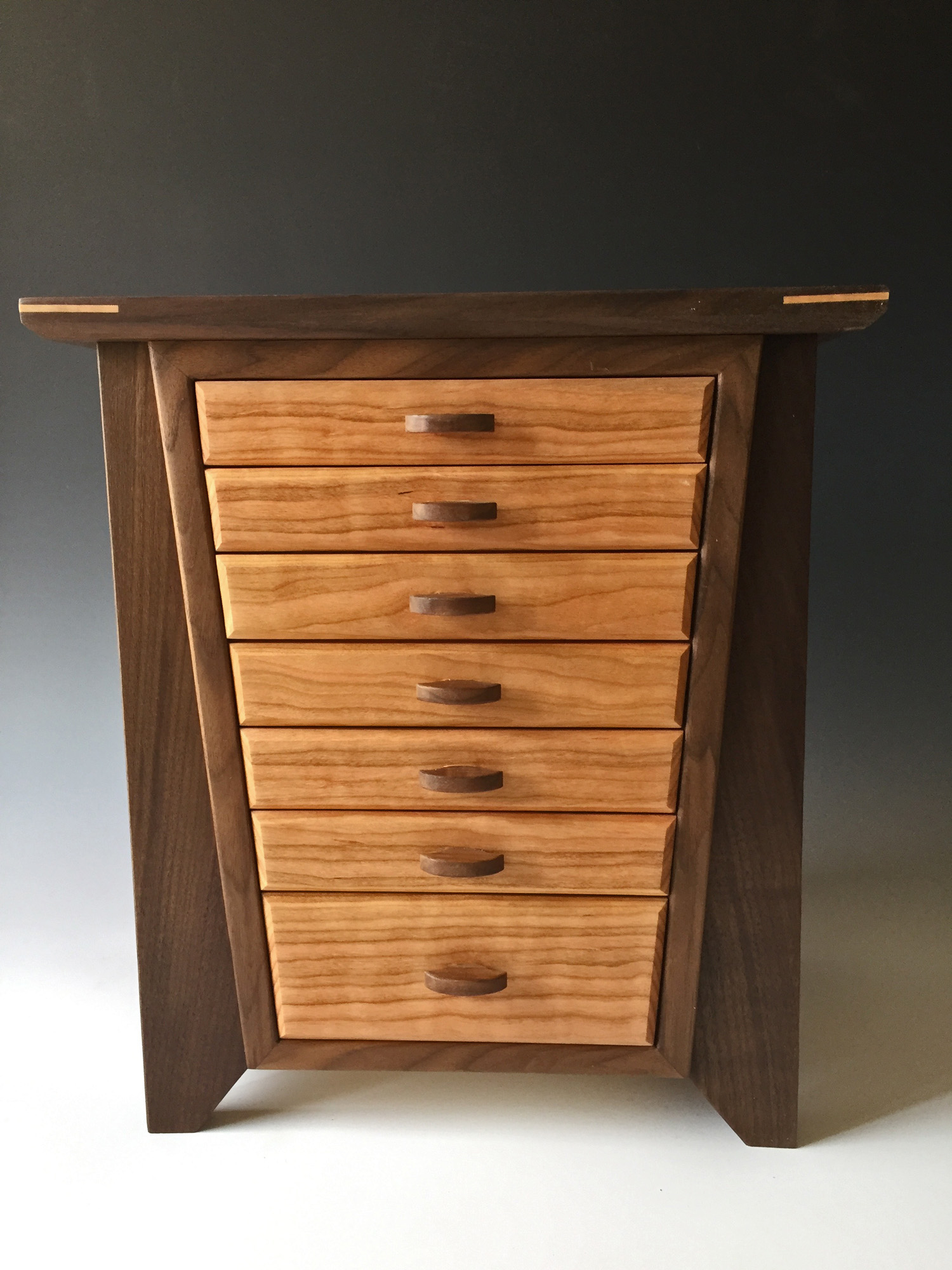 A photo of one of the most popular of my quality jewelry boxes, The Angle, shown in black walnut wood with curly natural cherry accents.