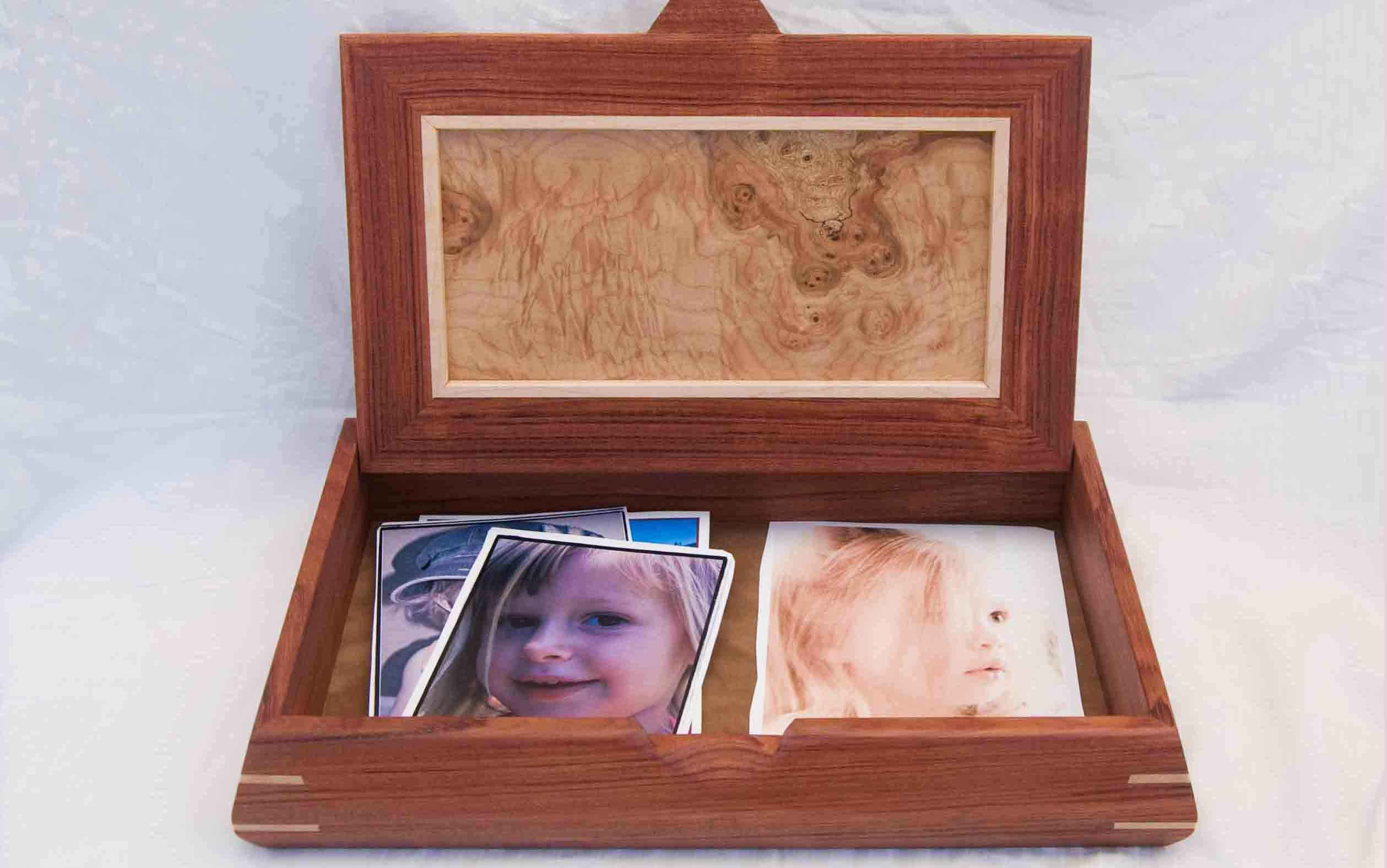 Handcrafted wooden box made of beautiful woods show with the lid open and holding photos