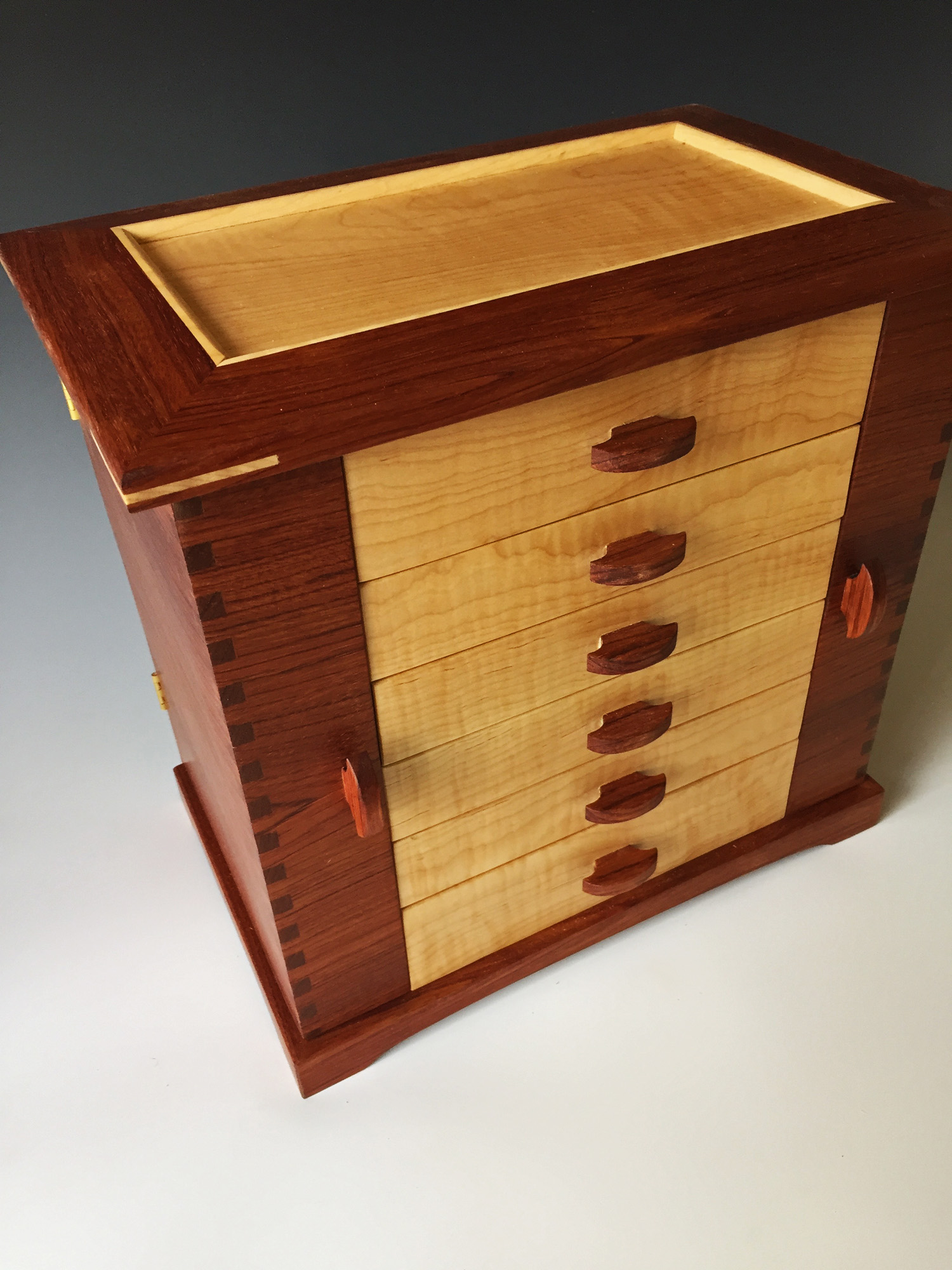 Photo of one of my large jewelry boxes, the Swingdoor, shown in bubinga redwood and curly maple wood drawers.
