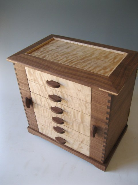 Image of a wooden jewelry box made of black walnut and quilted maple woods.